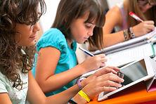 учител помага на дете да учи онлайн