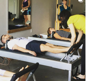 MeJo using her hands to help guide the feet of another teacher. Credit: Voltage Pilates - Instagram