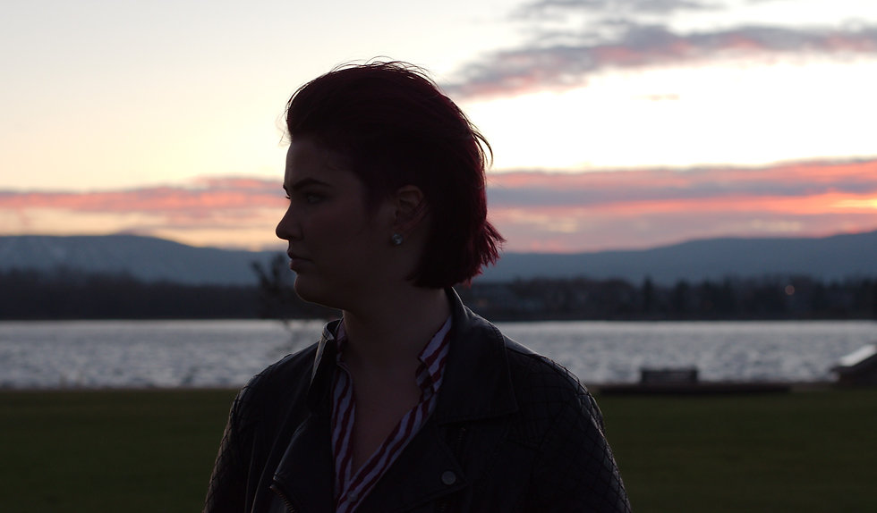 Sydney Riley with red hair, looking to the left with a sunset in the background