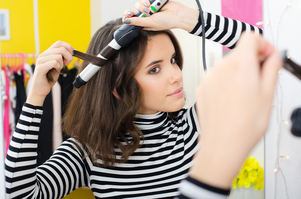 Young woman curling her hair.