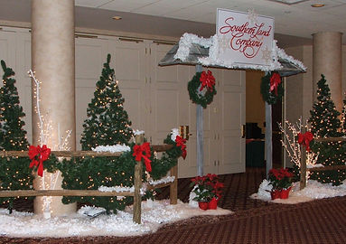 Christmas Party Entrance Decor - Trees with twinkling lights, snow, split-rail fences, red bows.