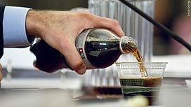 Hand pouring bottle of soda