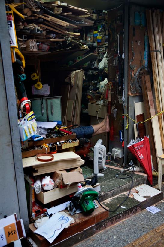A hardware shopkeeper props their feet up, Guangzhou, 2018