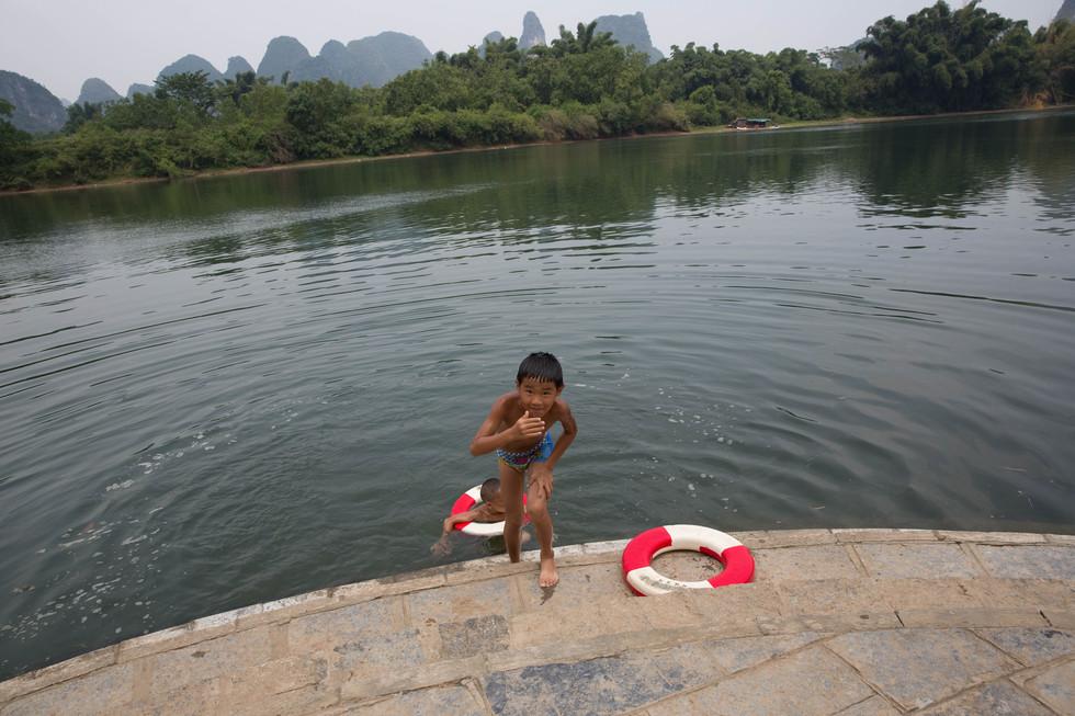 Children play in the Li River, Guangxi Region, 2018