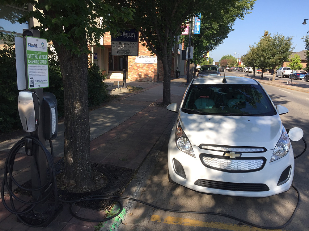 An electric car charging on-street in Okotoks