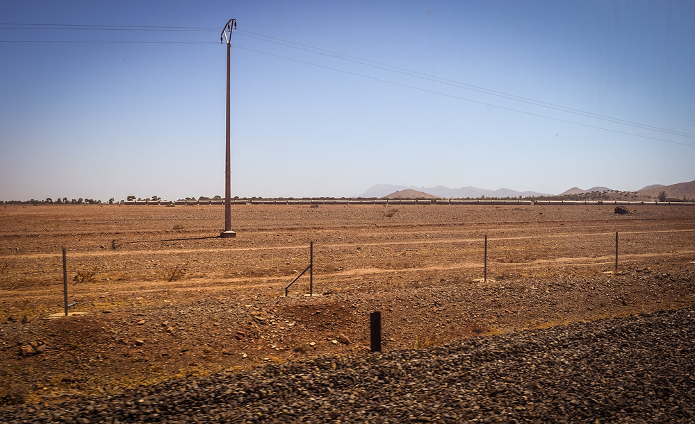 A telegraph pole, in an arid landscape, seen through the window of a moving train window in Morocco.