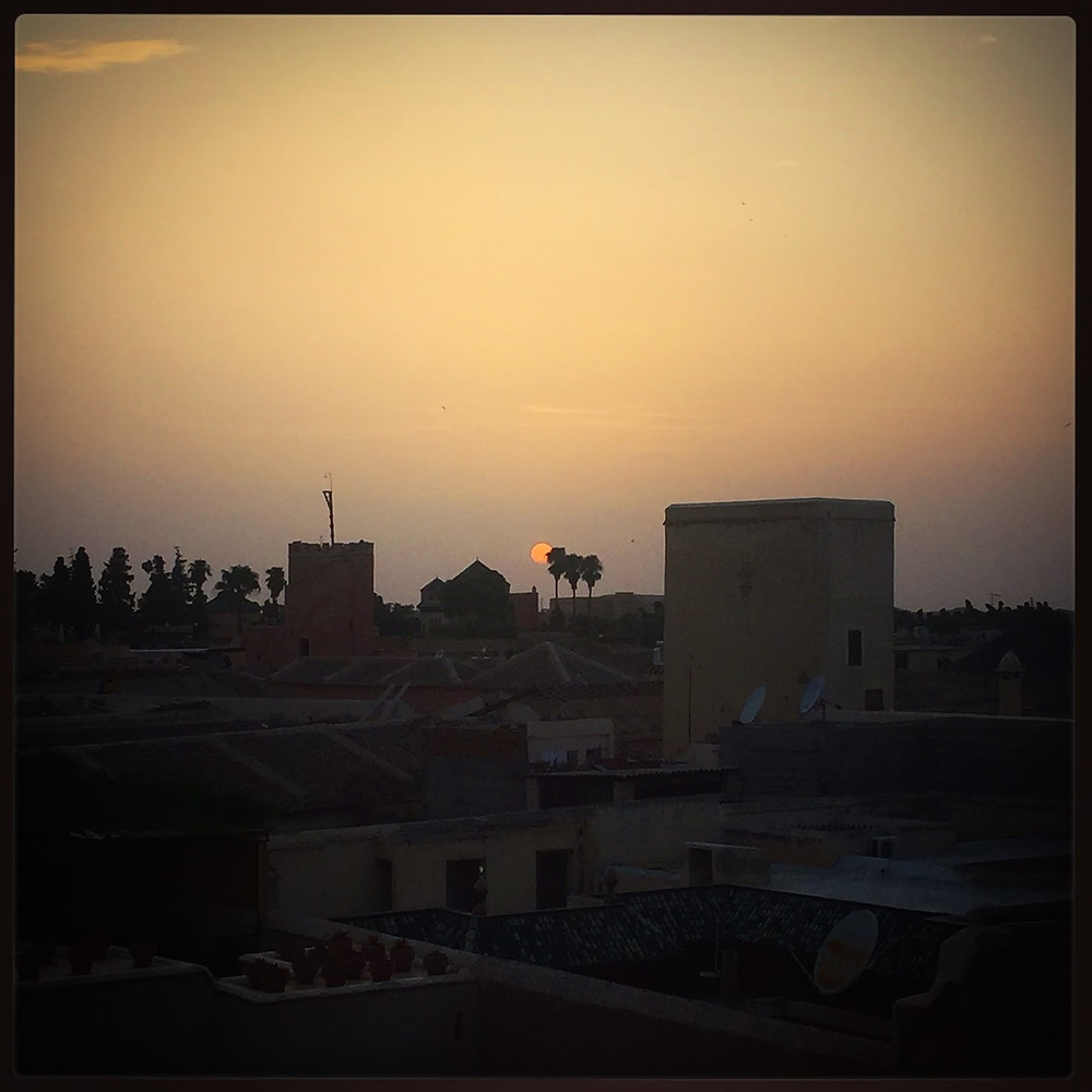 The sun setting behind distant palms, seen from the roof of Equity Point.