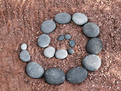 spiral of river stones on red earth