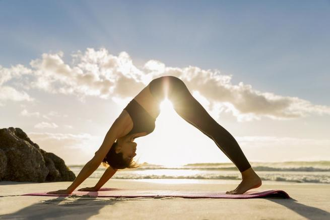 a-woman-practicing-yoga-on-the-beach_c