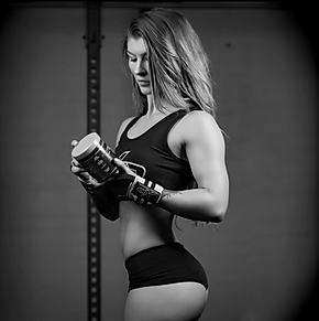 An XCD Nutrition female athletic holding onto a tub of Vapor XS.
