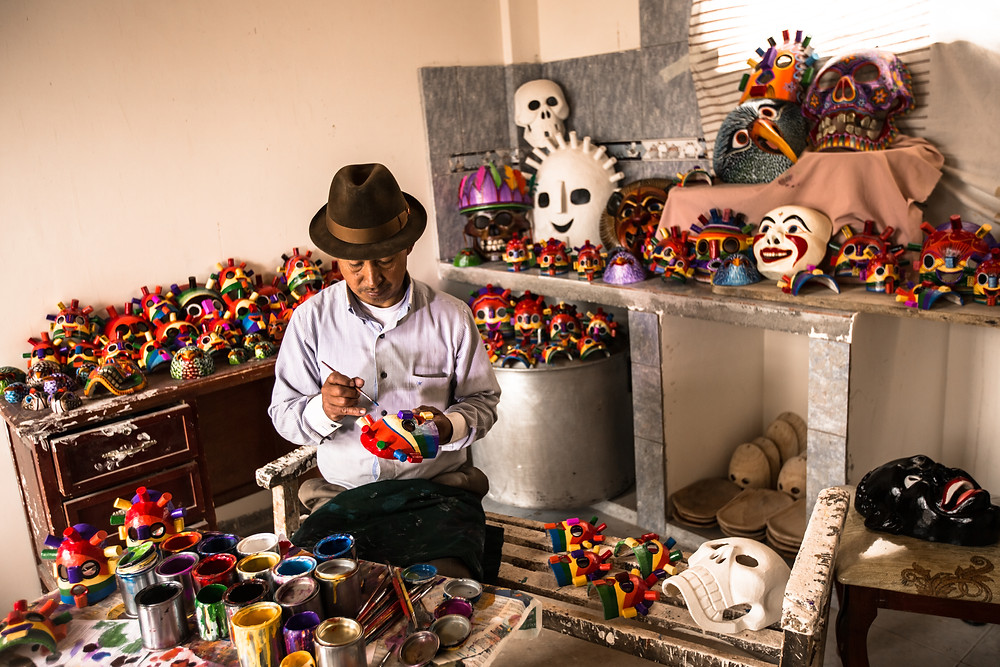 A man painting Day of the Dead Masks in Ecuador with Quasar Expeditions.
