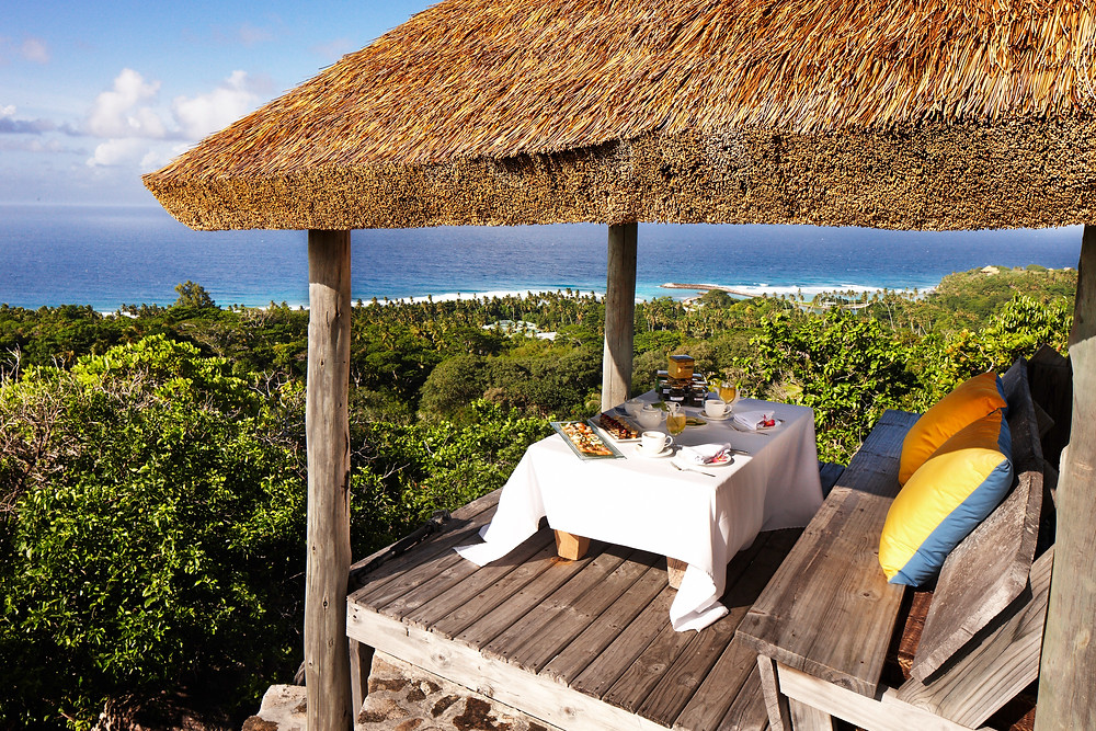 An outdoor dinning spot at Fregate Island Private overlooking the Indian Ocean.