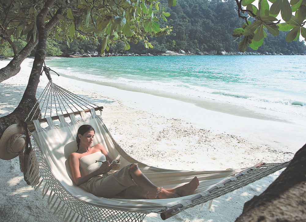 Woman relaxing in hammock at Pangkor Laut Resort, a YTL Hotel.