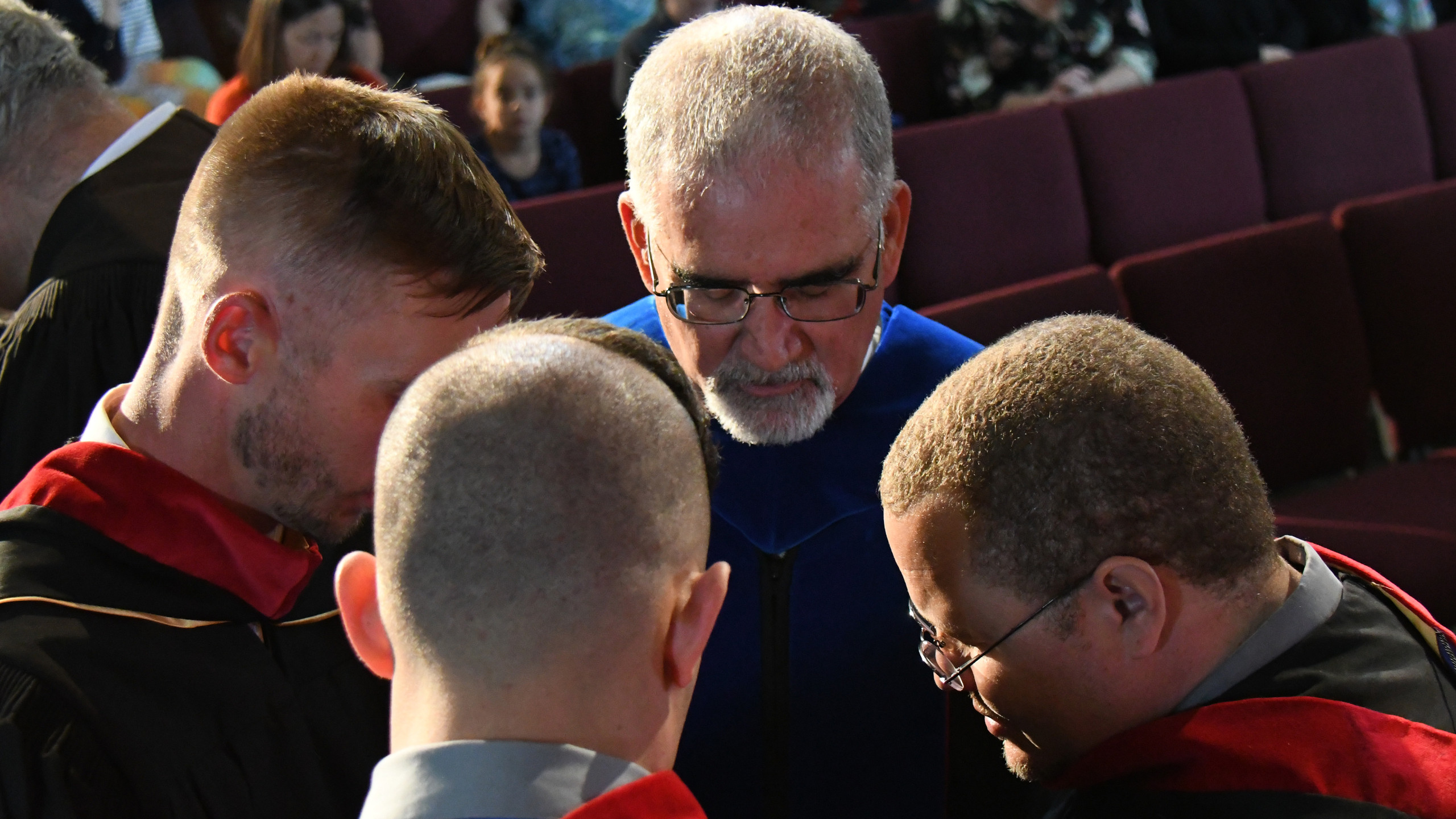 Gateway Seminary Rocky Mountain Campus Director Dr. Steve Veteto praying with Mark and other students as they embark upon the next phase of their lives and ministries.