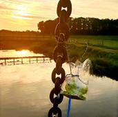 Aan een brug, bungelend in de zon, mijmerend over het water.