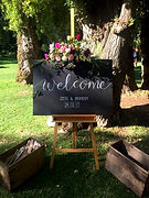 welcome chalkboard on easle with flowers
