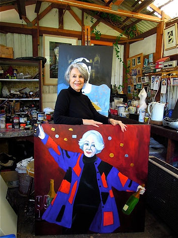 An image of Diana Marlay Cole in her studio with her paintings