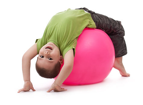 Little boy doing gymnastic exercises wit