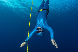 Lady freediver descending along the rope