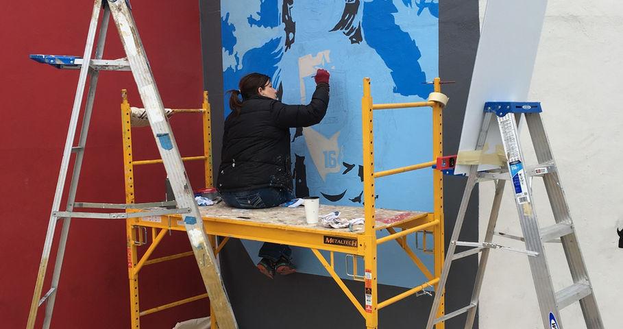 Amy painting Doug Mural
