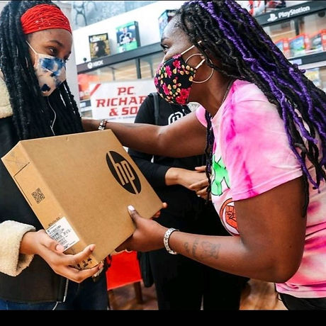 Black women gives a laptop to a Black child