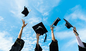 Four graduates throwing graduation hats