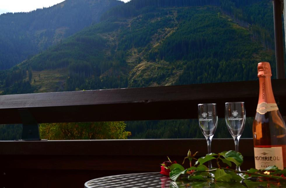 Balkon mit Sektflasche und Rose