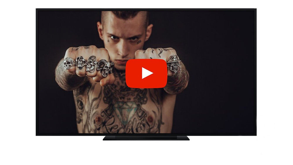 a widescreen tv with a programme screenshot of  a tattooed man and a youtube play button