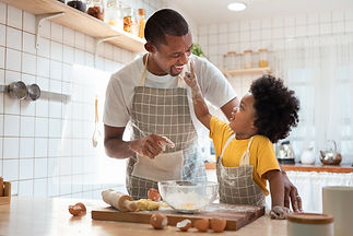 African family have fun cooking baking c