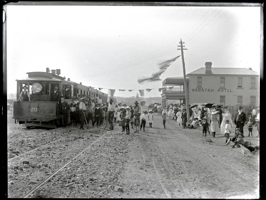 B&W tram on left, hotel on right and a crowd of Federation partiers between