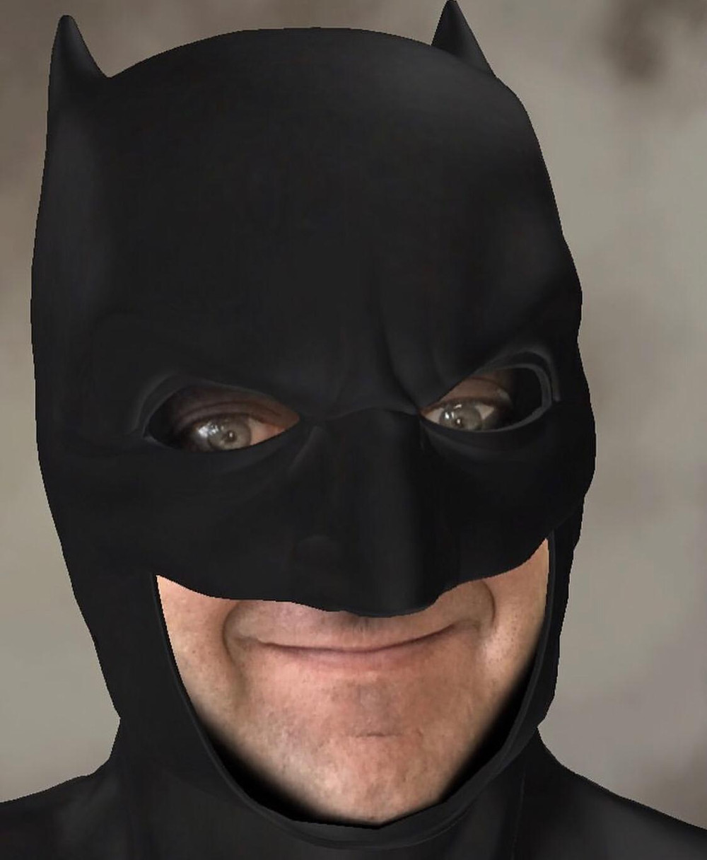 Man with fair skin and green eyes, wearing a Batman costume (headshot only)