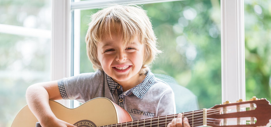 Happy smiling boy learning to play the a