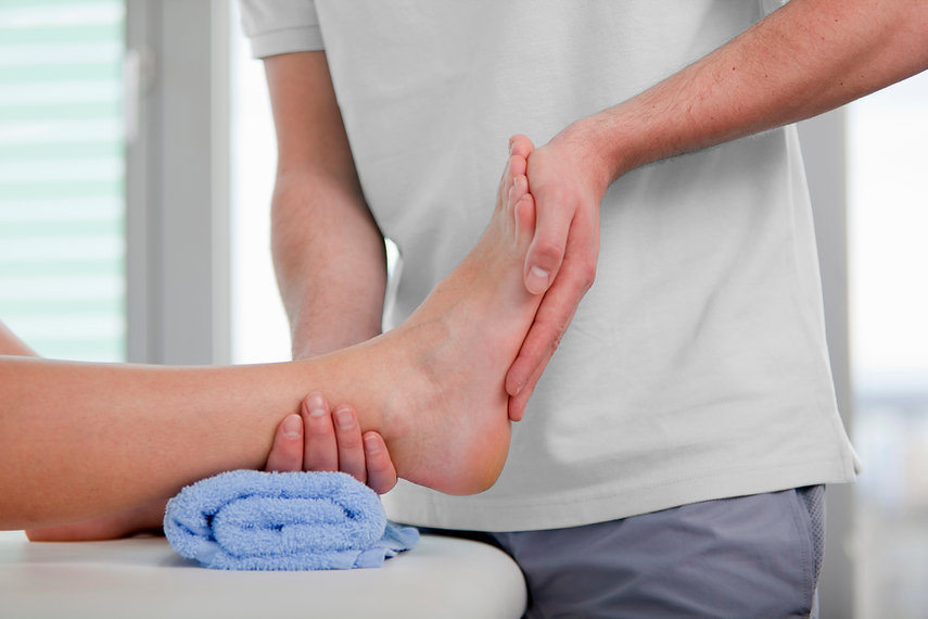 A person massaging a foot that's resting on a towel.