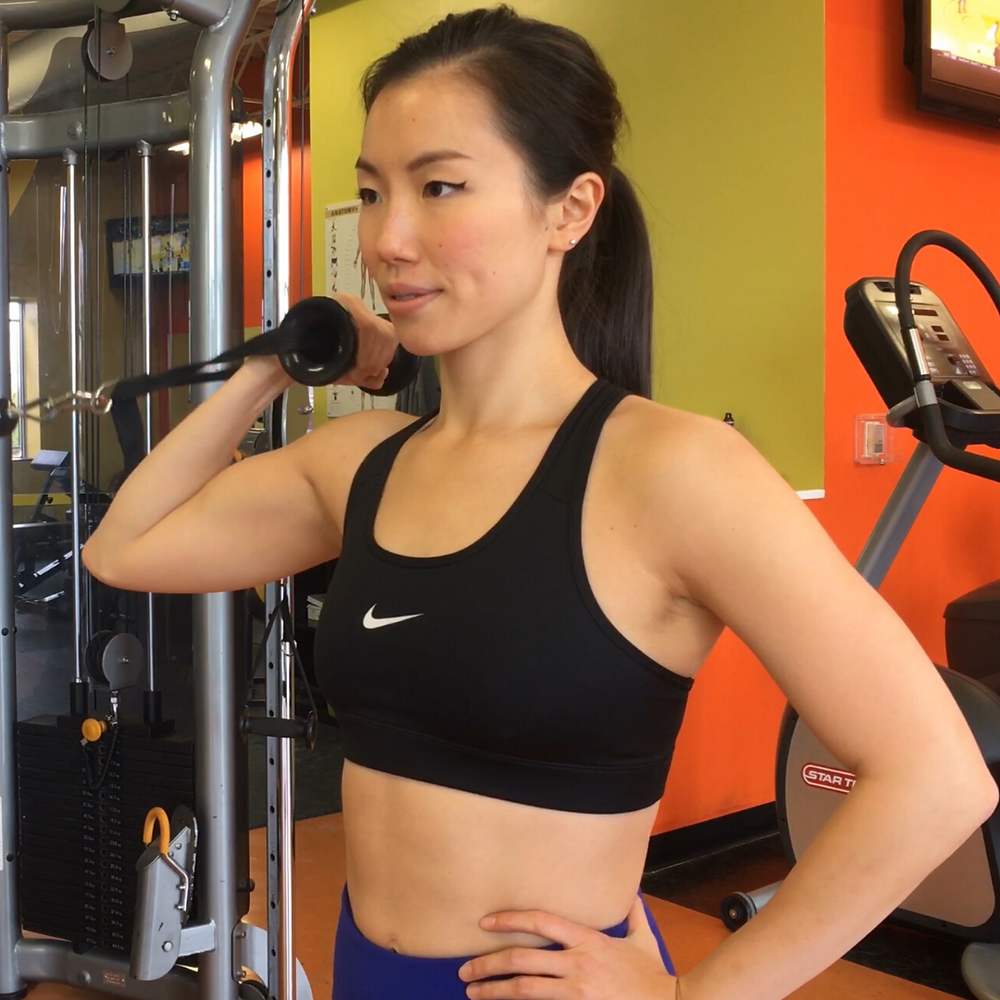 girl doing a biceps curl with a cable machine