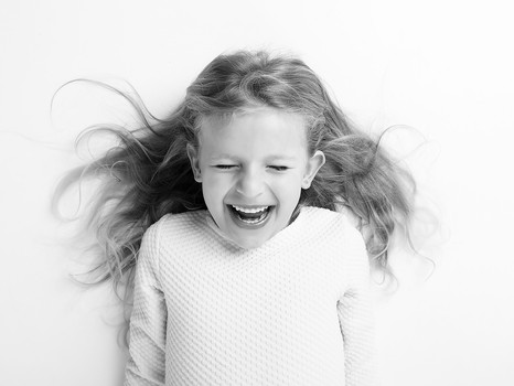 rozesmátá holčička s dlouhými vlasy na fotce
