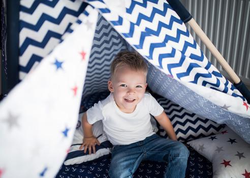 chlapeček vykukuje v teepee stanu pro děti