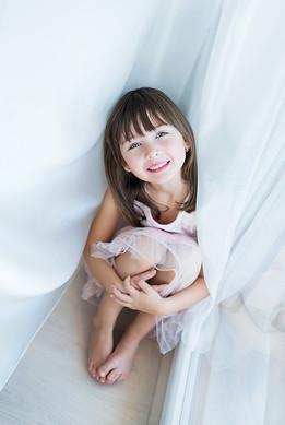 portrét holčičky u okna se záclonou