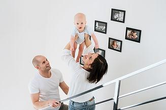 rodina s miminkem s fotoobrazy nad schodištěm