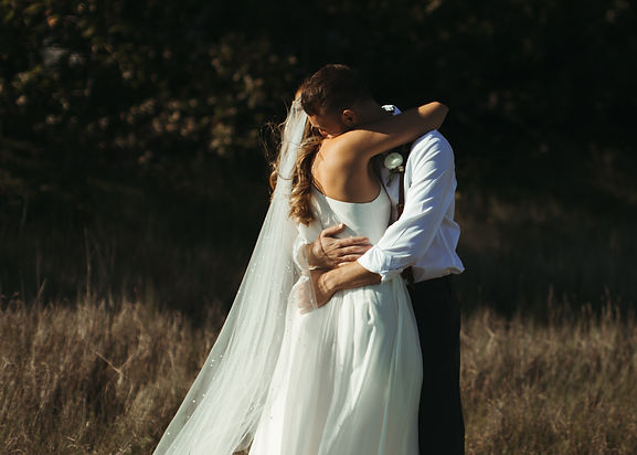 Bride and groom hugging in tall grass