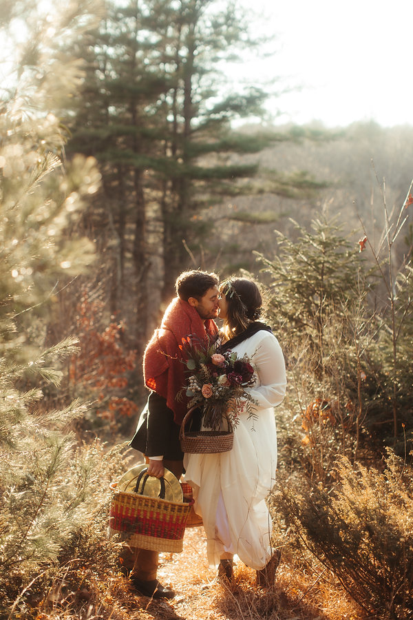 non traditional wedding bride and groom elope on mountain first kiss