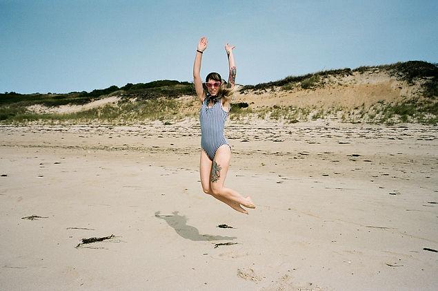 nikki bassette photographer jumping on beach in vintage swim suit
