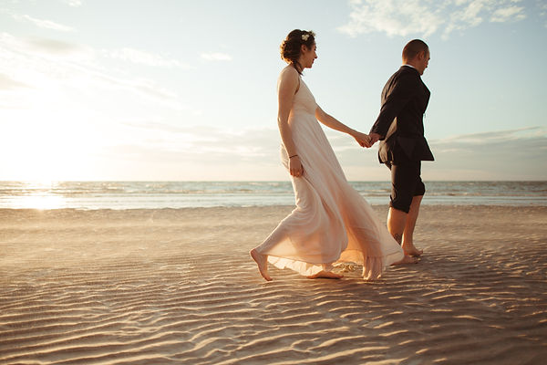 cape cod bride and groom holding hands on beach