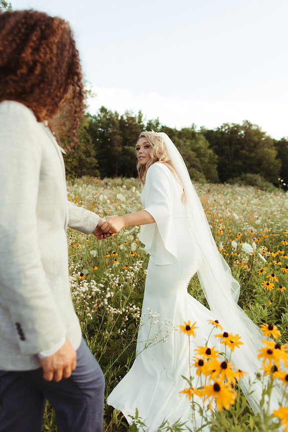 Bride and groom in flower field shot by nikki bassette photography