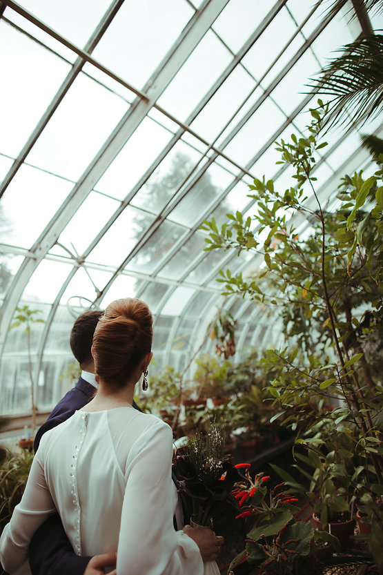 bride and groom in green house