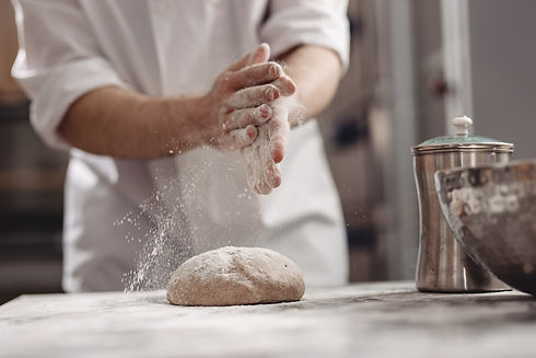 baker-adds-flour-to-dough-on-the-table-i