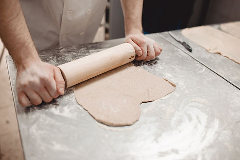 baker-is-rolling-dough-on-the-table-in-t