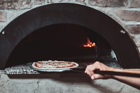 chef-put-pizza-to-the-oven-for-baking-GK