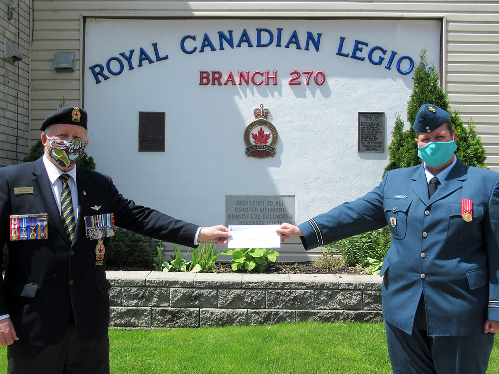 While respecting COVID-19 convention, Coldwater Branch President Norm Marion (left) presents a donation of $500 to Capt Megan McKinnon, Commanding Officer of 724 Midland Lions Air Cadet Squadron.
