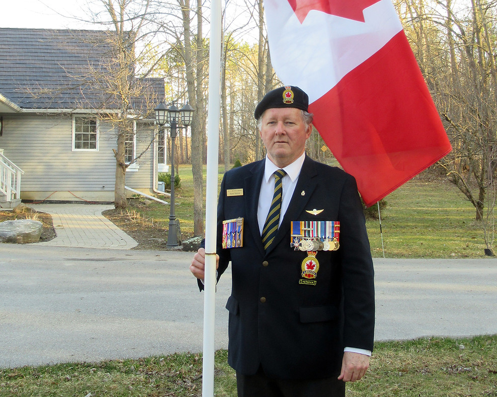 Coldwater Legion Branch President Normand Marion lowers the National Flag at his home, a reminder for everyone to stay home and stay safe.