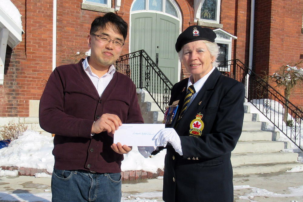 Comrade Betty-Jean Murray (right), presents a cheque for $200 to Reverend Bright Yun of the Coldwater United Church